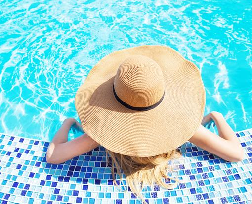 woman in pool with summer hat