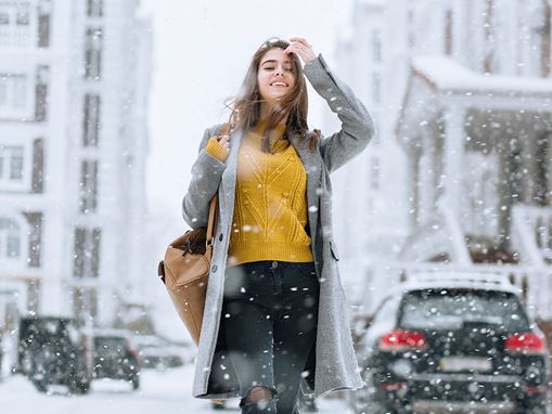 Woman in a city with falling snow flakes