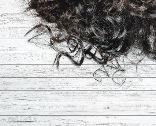 Perm curls on white wooden background